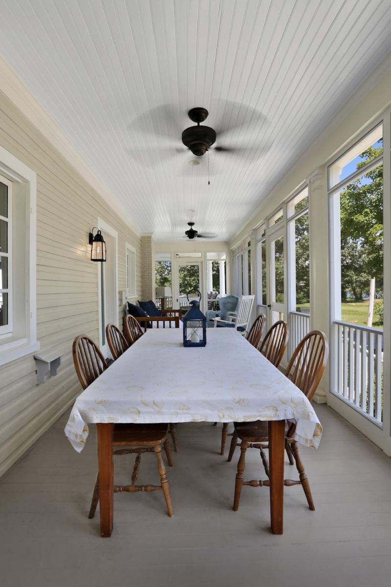 Outdoor dining area on screened porch.